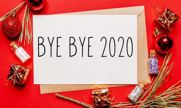 Kartka świąteczna żegnaj 2020 z prezentem, gałązką jodły i zabawką na czerwonej odizolowanej powierzchni. koncepcja nowego roku