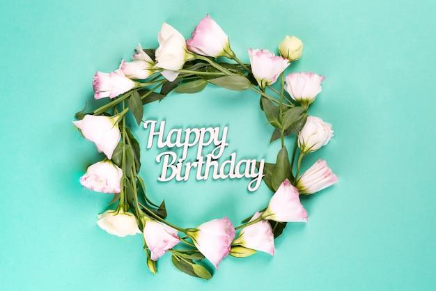 Kartka urodzinowa. wieniec wykonany z eustoma różowych kwiatów na niebieskiej powierzchni