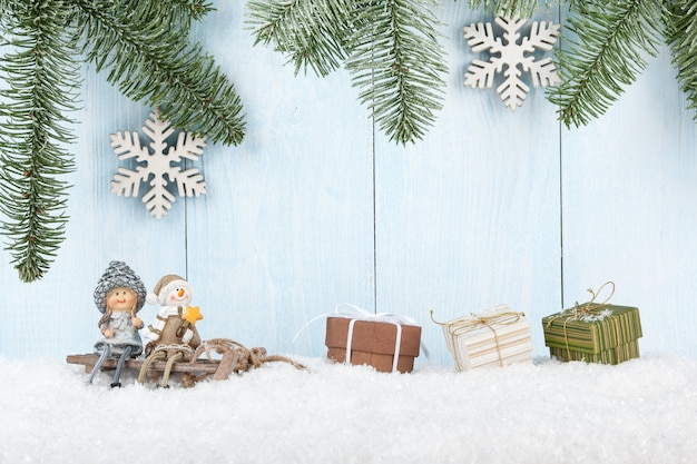 Kartka wesołych świąt z uśmiechniętymi figurkami na saniach i pudełkami na prezenty