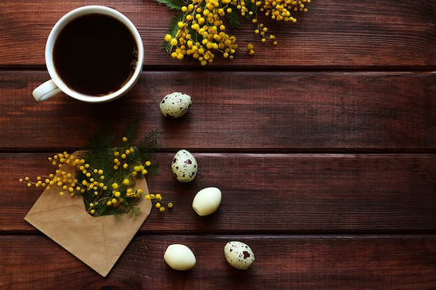 Kartka wielkanocna kwiaty mimozy, słodycze w kształcie jaj przepiórczych i filiżanka kawy