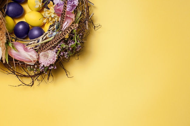 Kartka wielkanocna. malowane pisanki w gnieździe na żółto