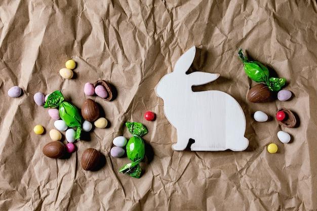 Kartka wielkanocna z drewnianymi dekoracjami królika, czekoladowymi słodyczami i jajkami na pomiętym papierze rzemieślniczym