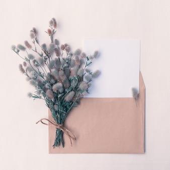 Kartka z bukietem dzikich puszystych kwiatów w kopercie z miejscem na kopię na projekt