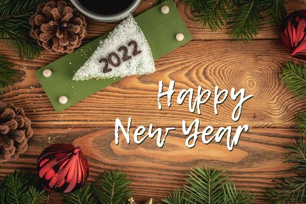 Kartka z kawałkiem białego świątecznego tortu ozdobionego cyfrą 2022 z czekolady i napisem happy new year. widok z góry