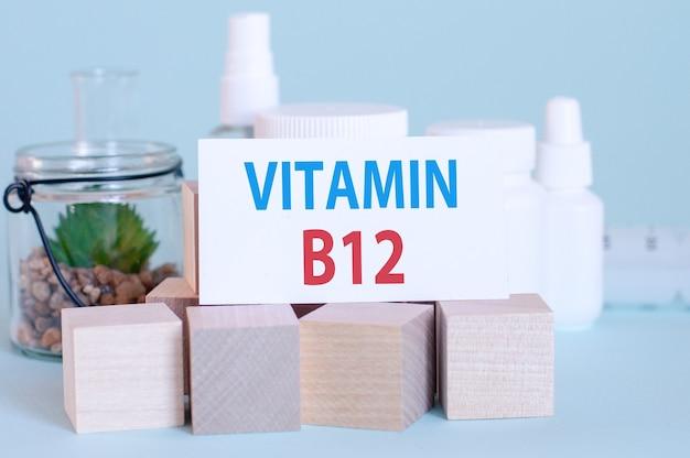 Kartka z napisem witamina b12 na tle leków i drewnianych kostek, niebieskie tło, selektywna ostrość