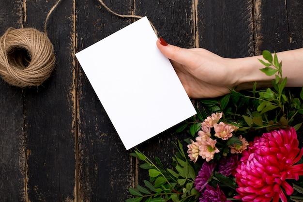 Kartka z pozdrowieniami w ręce z bukietem kwiaty na ciemnym rocznika drewnie