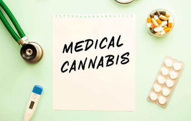 Kartka z tekstem medical cannabis, stetoskop i lekarstwa. pojęcie medyczne.