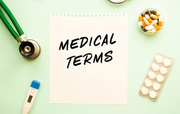 Kartka z tekstem warunki lekarskie, stetoskop i lekarstwa. pojęcie medyczne.