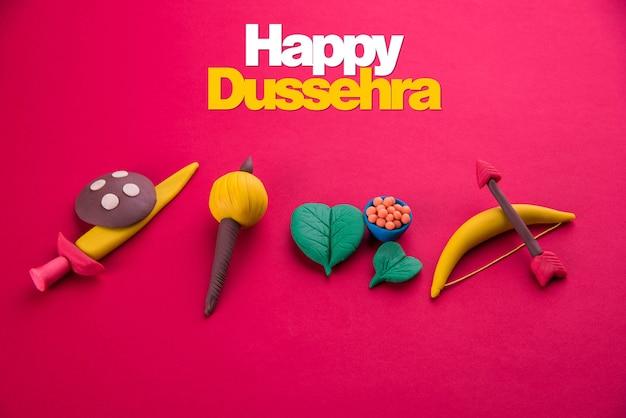 Kartka z życzeniami happy dasera lub ayudh puja przedstawiająca zdjęcie glinianego modelu ramion używanego w ramajanie i mahabharacie