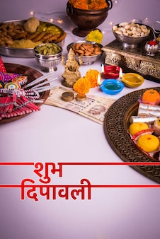 Kartka z życzeniami happy diwali przedstawiająca lampę naftową lub diyę z krakersami, mithai, suszonymi owocami, banknotami indyjskiej waluty, kwiatem nagietka i posągiem bogini laxmi lub lakshmi
