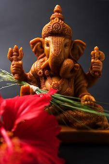 Kartka z życzeniami happy ganesh chaturthi przedstawiająca fotografię idola lorda ganesha z pooja lub puja thali, bundi laddu/modak, durva i hibiskusem lub kwiatem jasvand