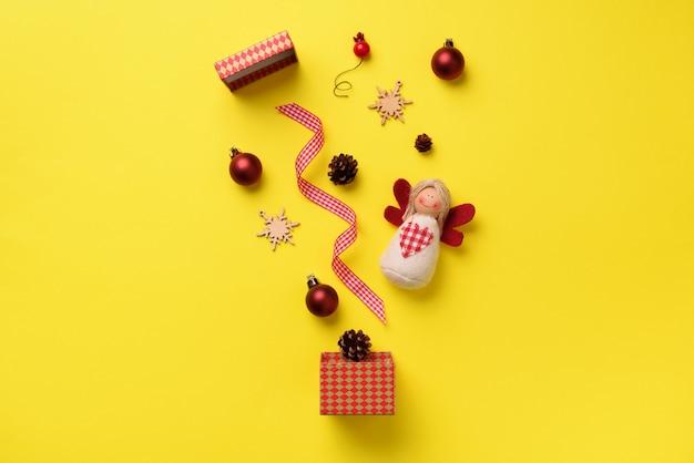 Kartka z życzeniami na imprezę noworoczną. boże narodzenie prezenty, elementy dekoracyjne i ozdoby na żółtym tle.