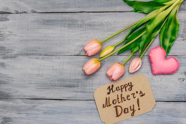 Kartka z życzeniami na szczęśliwy dzień matki. delikatne różowe tulipany, ręcznie robione filcowe serce