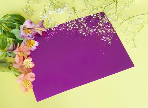 Kartka z życzeniami z kwiatami. sztandar z alstroemeria kwitnie na różowym tle.