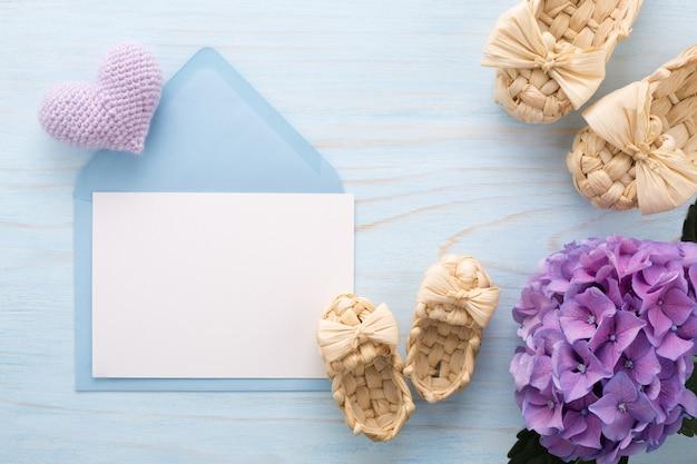 Kartkę z życzeniami na dzień matki z kwiatami bzu i botkami dla niemowląt.