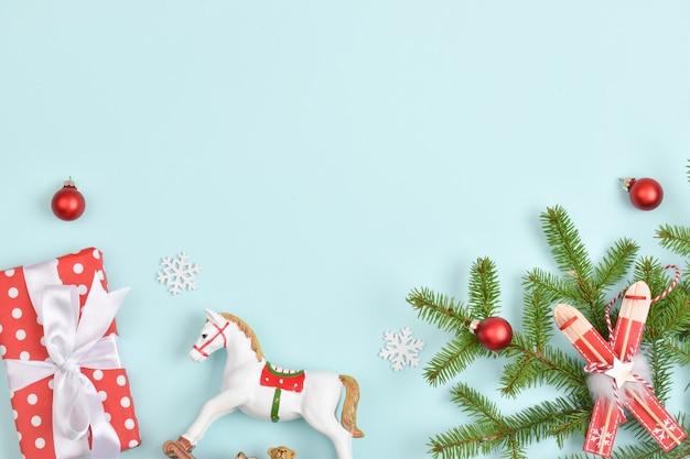Kartkę z życzeniami na nowy rok i boże narodzenie. świąteczny baner z prezentami i świątecznymi zabawkami na jasnoniebieskim tle. płaski układ, widok z góry. skopiuj miejsce.