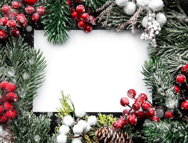 Kartkę z życzeniami na święta bożego narodzenia. świerkowe gałęzie, szyszki i czerwone jagody. widok z góry