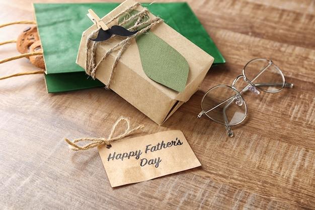 Kartkę z życzeniami, prezenty i okulary na drewnianym stole. kompozycja na dzień ojca