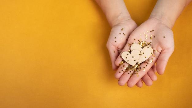 Kartkę z życzeniami symbol miłości walentynki romantyczne serce w ręce kobiety na żółtym tle z...