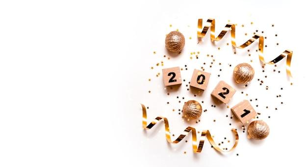 Kartkę z życzeniami szczęśliwego nowego roku 2021 ze złotymi wstążkami i bombkami