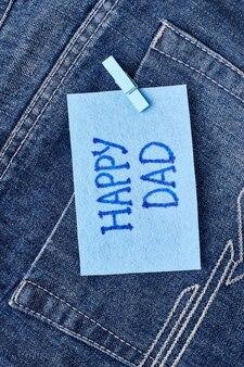 Kartkę z życzeniami szczęśliwego taty. papier z pozdrowieniami na kieszeni dżinsów. pogratuluj tatusiowi.