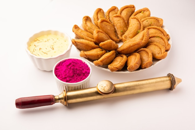 Kartkę z życzeniami szczęśliwy holi. słodki jalebi, jilapi, zulbia, mushabak lub zalabia z napojem thandai i kolorem gulal ułożonym na białym
