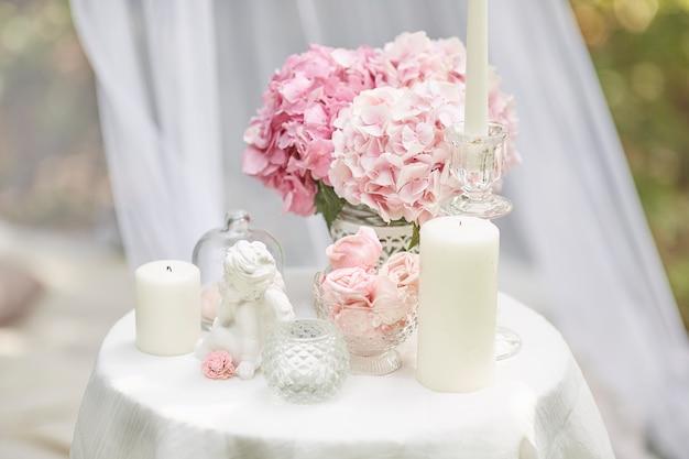 Kartkę z życzeniami w stylu shabby chic. kwiaty hortensji, figurka anioła, pianki, świece na stole.