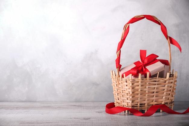 Kartkę z życzeniami walentynki z serca, czara i prezenty w koszu na podłoże drewniane. z miejscem na powitanie tekstowe