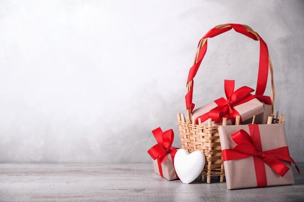 Kartkę z życzeniami walentynki z serca i prezenty w koszu na drewniane tła. z miejscem na pozdrowienia tekstowe