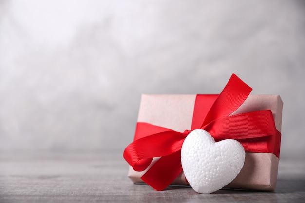 Kartkę z życzeniami walentynki z serca na tle drewniane i prezent. z miejscem na pozdrowienia tekstowe