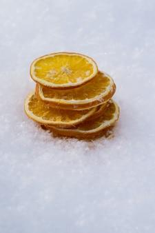 Kartkę z życzeniami wesołych świąt i nowego roku z suchej pomarańczy, mandarynki clementines na śniegu