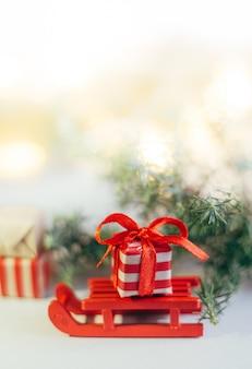 Kartkę z życzeniami wesołych świąt i wesołych świąt, ramki, baner. nowy rok. gałęzie drzewa zimozielonego. świąteczne pudełko na drewniane sanki. pudełko z czerwoną wstążką.