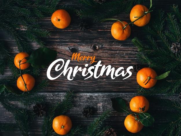 Kartkę z życzeniami z napisem wesołych świąt na drewnianym tle z mandarynki oddział jodła