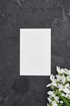 Kartkę z życzeniami z przebiśniegami na ciemnoszarym tle
