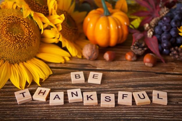 Kartkę z życzeniami z tekstem bądź wdzięczny. kompozycja z dyni, jesiennych liści, słonecznika i jagód na drewnianym stole. przytulna koncepcja jesiennego nastroju