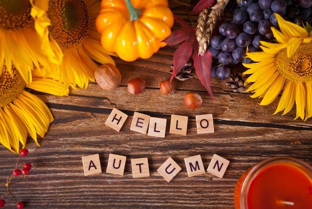 Kartkę z życzeniami z tekstem hello jesień. kompozycja z dyni, jesiennych liści, słonecznika i jagód na drewnianym stole. przytulna koncepcja jesiennego nastroju