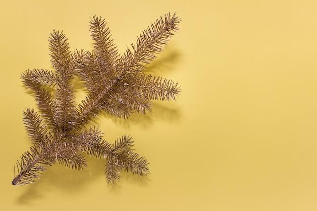 Kartkę z życzeniami z złoty wiecznie zielony oddział boże narodzenie na żółtej powierzchni