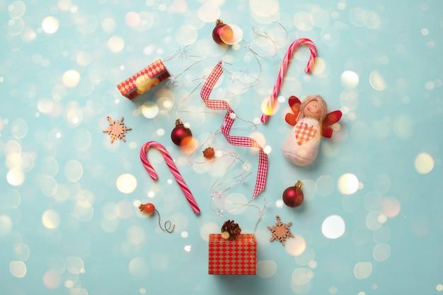 Kartkę z życzeniami ze śniegiem, światła bokeh na imprezę nowego roku. boże narodzenie prezenty, elementy dekoracyjne i ozdoby na niebieskim tle.