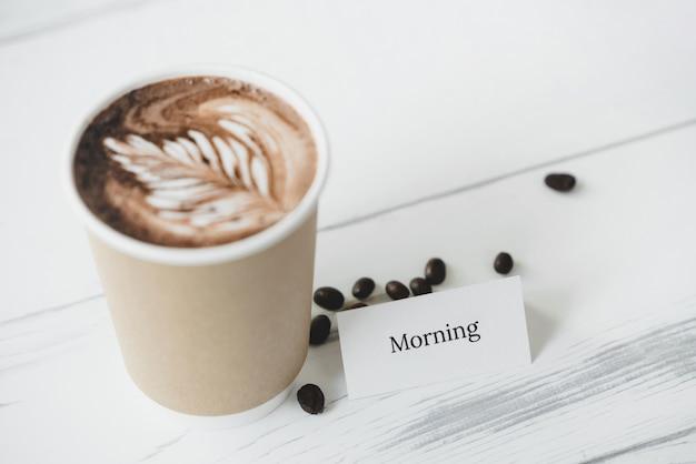 Kartkę z życzeniami ze świeżo parzoną kawą latte art w filiżance na wynos