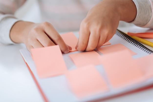 Kartki samoprzylepne. zamknij się różowe karteczki, które są wprowadzane do zeszytu przez miły, przyjemny, zachwycony dzieciak