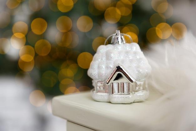 Kartki świąteczne i tło. boże narodzenie szklane białe zabawki dom w śniegu, na tle żółtego bokeh świateł wianek