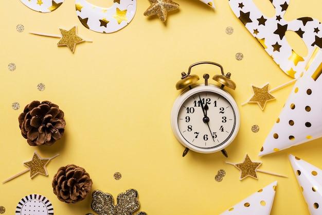 Kartki świąteczne z czapeczki, maski i zegar na żółtym tle.
