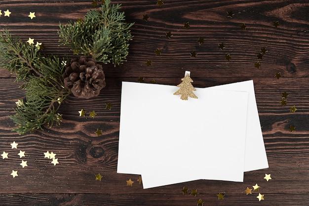 Kartki świąteczne z gałązek jodły i złotych gwiazd na vintage drewniane tła.