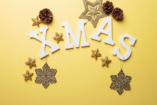 Kartki świąteczne z literami i świąteczną dekoracją na żółtym tle. koncepcja bożego narodzenia, widok z góry na dół