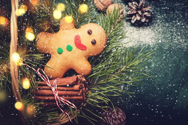 Kartki świąteczne z piernika i gałęzi drzew iglastych w koszu.