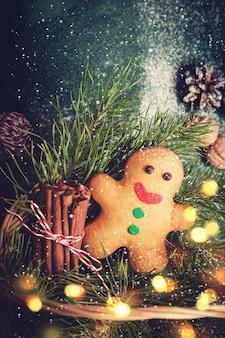 Kartki świąteczne z piernika i gałęzi drzew iglastych w koszu