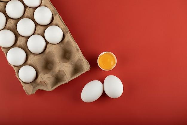 Karton białych jaj z żółtkiem na czerwonej powierzchni.
