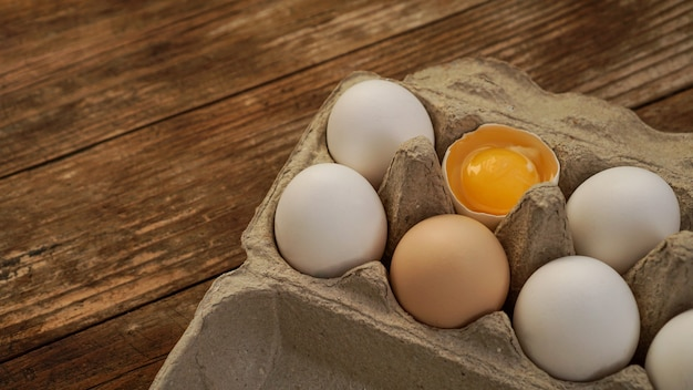 Karton białych jajek i pęknięte jajko pół z żółtkiem widok z góry na drewniane tła. koncepcja gotowania na śniadanie wielkanocne i zdrowe jedzenie