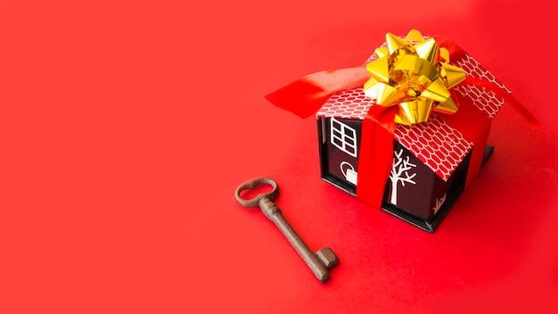 Karton dom z kokardą i wstążką w pobliżu klucza
