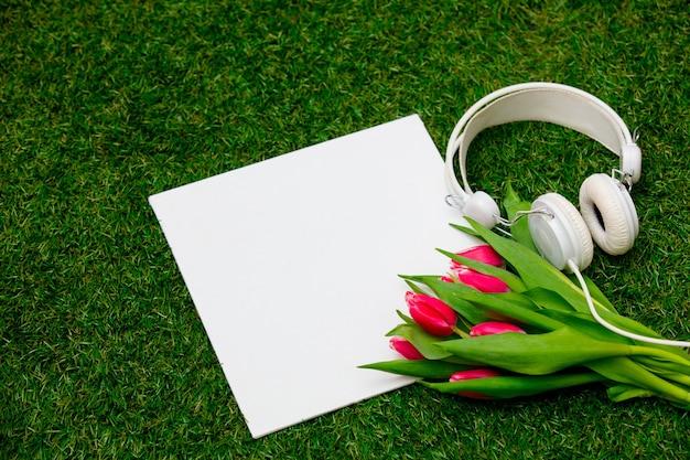 Karton i tulipany ze słuchawkami na zielonej trawie